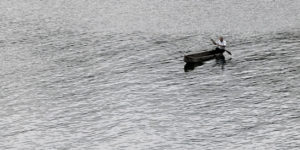 an old man rows a small canoe acorss a lake